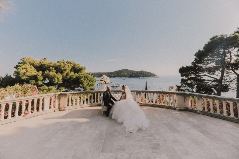 The couple is outside on the terrace of villa Sheherezada in Dubrovnik. In the background is Lokrum island, around them are trees. They are sitting and holding hands.