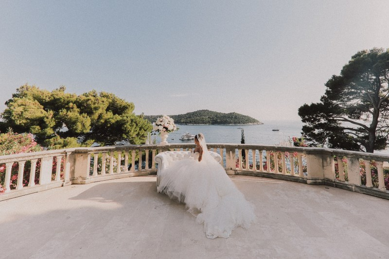 This photo shows the bride in Villa Sheherezade in Dubrovnik. She is sitting all alone on the big terrace, facing the island in the background. Her wedding dress is a beautiful, huge, long white gown.