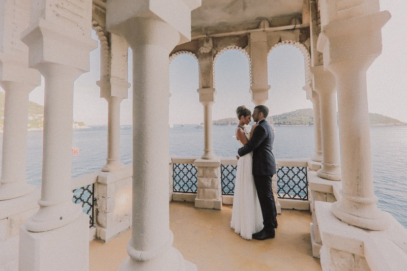 This is a beautiful couple during their photoshoot in Villa Sheherezade in Dubrovnik. They are in a stunning white pavillion with collumns, embracing each other.
