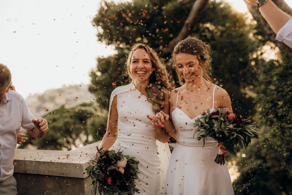 The two brides are arriving to their wedding ceremony in Slavica open air cinema in Dubrovnik. The guests are throwing confetti and the couple is laughing.