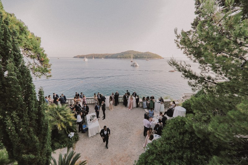 This is cocktail hour during a wedding in Villa Sheherezade. With a beautiful view of Lokrum island, guests are enjoying drinks from high white tables.