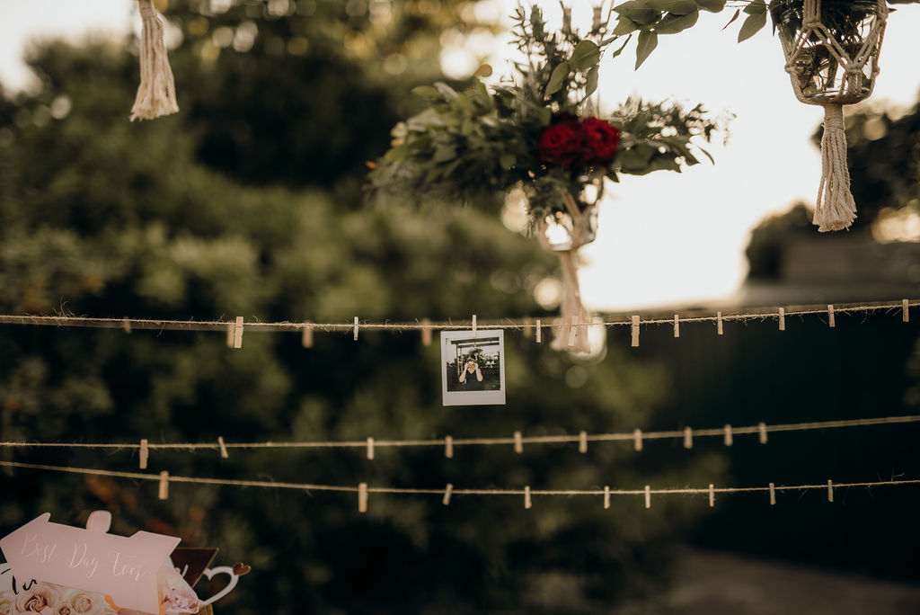 Dubrovnik wedding polaroid corner. There is only one polariod handing on the string for now, waiting for many others. Above the string there are flower arrangements of greenery and dark red roses.