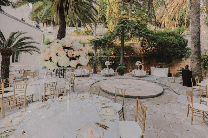 This image by Mihoci Studios shows a reception set up for a wedding in Sheherezade palace in Dubrovnik. There is a lot of greenery and palm trees around the circular table set up.