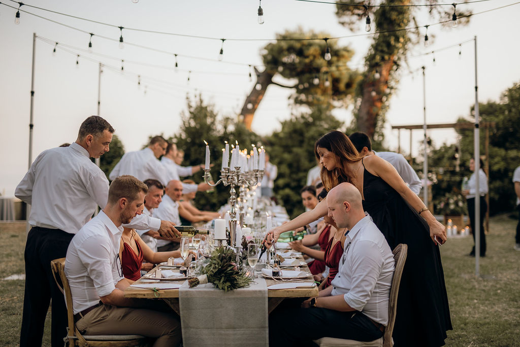 Dubrovnik wedding planner behind the scenes lighting candles. The guests are being served dinner. There are string lights above them and a white seethrough runner on the table.