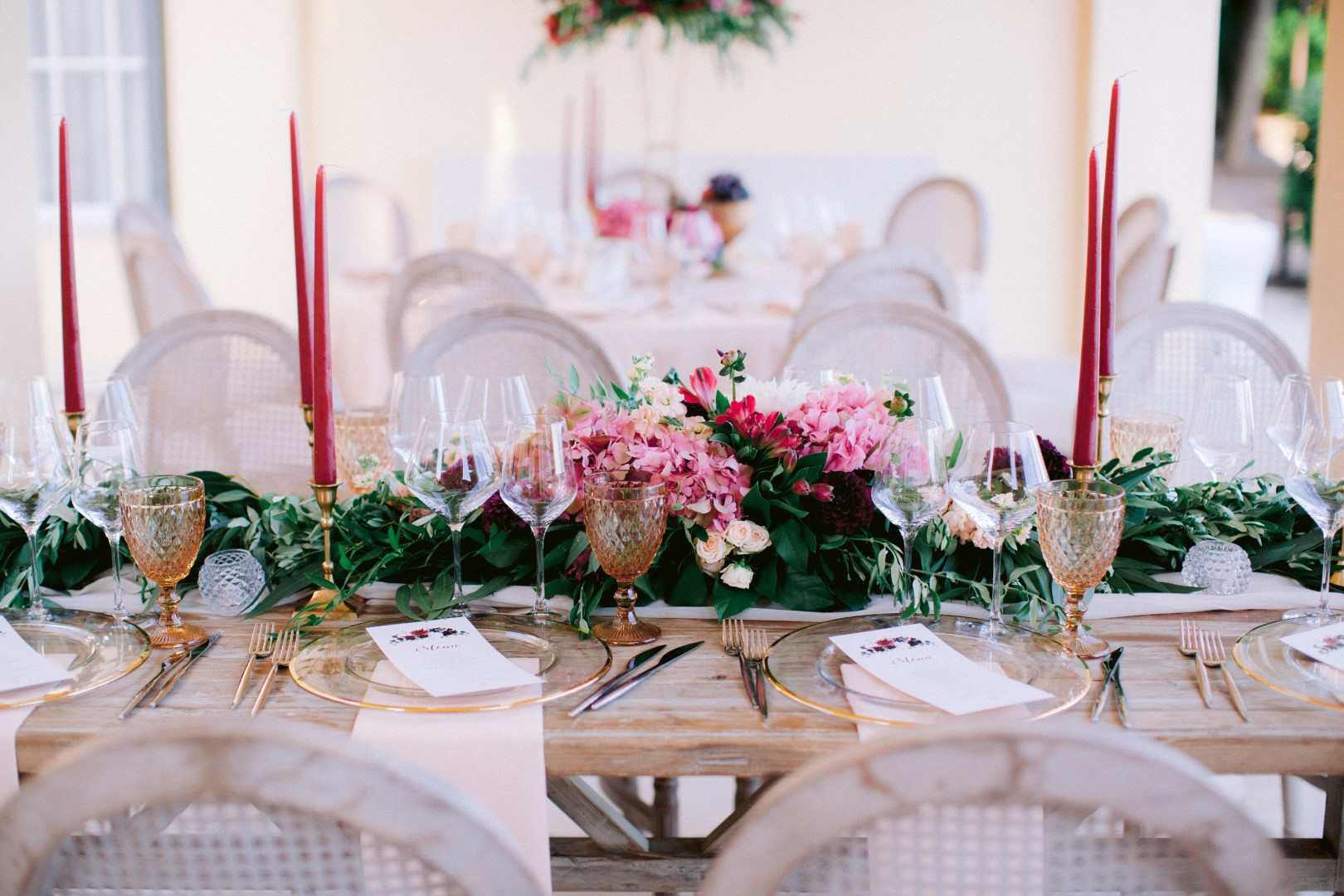 Split wedding Villa Dalmacija by Jona Christina photography. The flower arrangement is mainly pink flowers and greenery. The are tall dark pink candles and golden cups and cutlery.