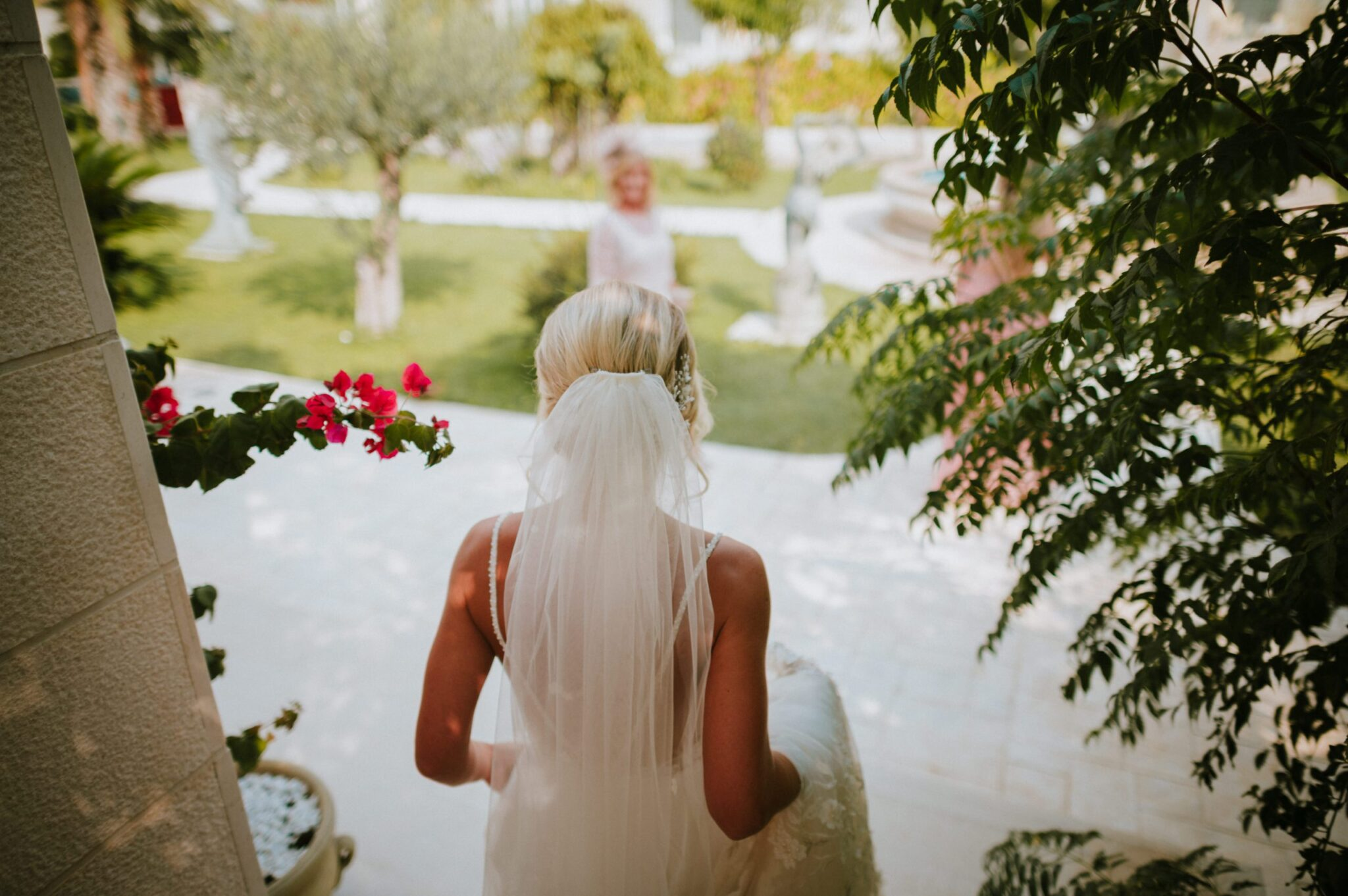 This image shows the bride from behind early in the day just as she got ready. She has an updo and a veil and she's holding her dress.
