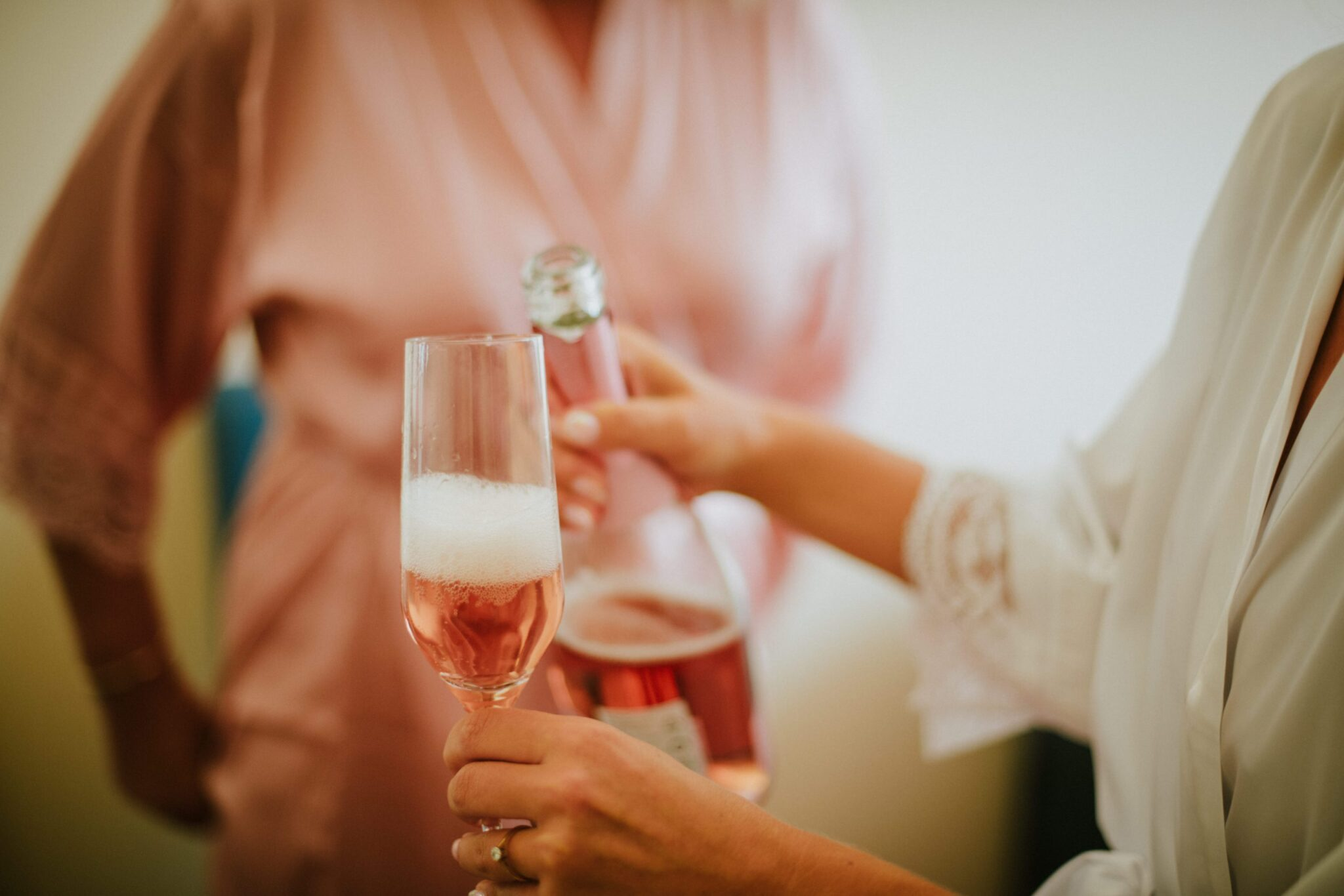 This is a photo of the bride sharing some prosecco with her bridesmaids. It's pink as well as the dressing gown of the bridesmaid in the background, while the bride has a white one. You can only see their hands, a glass and the bottle.