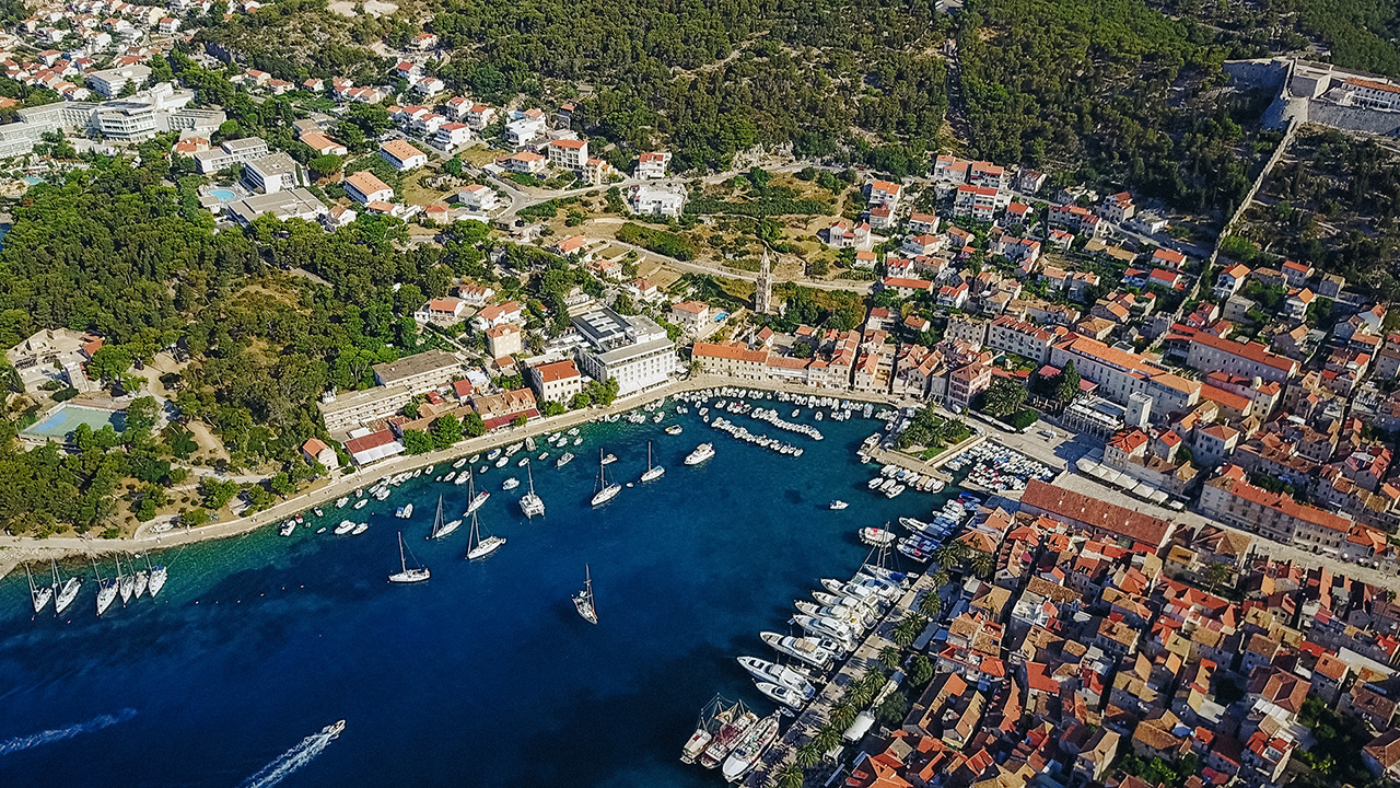 This image shows a coastal town in Dalmatia, Croatia. We can see the beautiful sea, lots of boats in the harbour and a fortress on the top of the village.