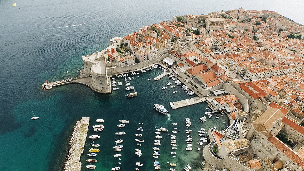 This image shows the old harbour of the old city of Dubrovnik. The sea is a dark blue and really brings out the red rooftops of the town.