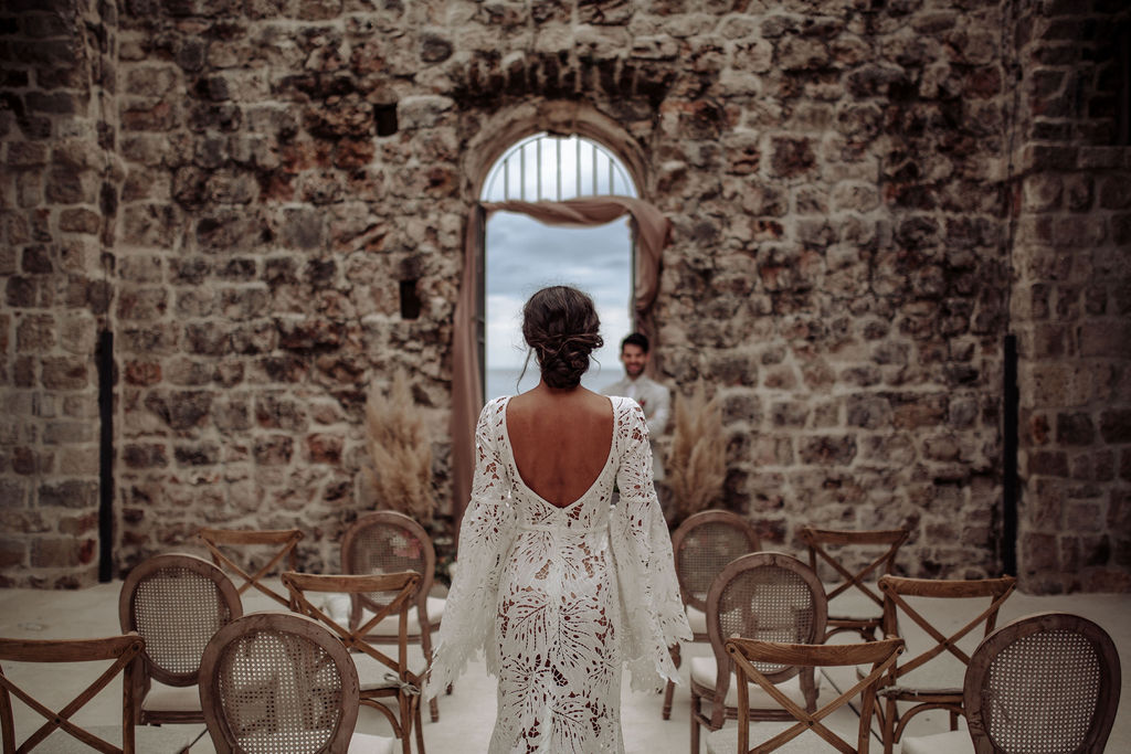 Image from a ceremony set up from a styled shoot for an elopement wedding in Lazareti, Dubrovnik. Around them are big limestone walls and the chairs are a combination of Louis and cross back chairs. The groom is smiling at the bride.
