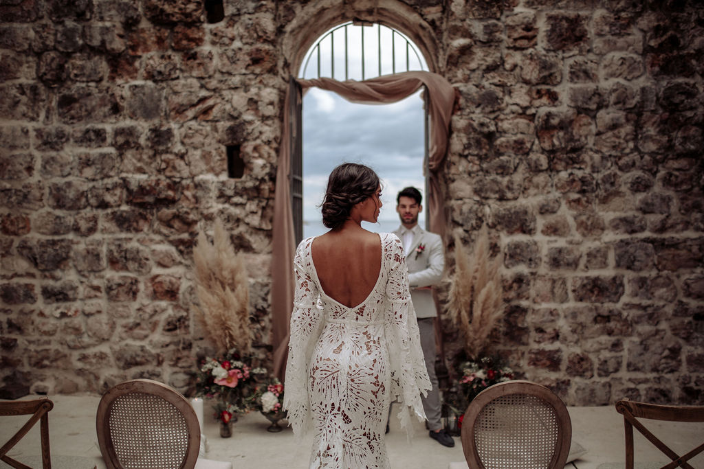 Image from a ceremony set up from a styled shoot for an elopement wedding in Lazareti, Dubrovnik. Around them are big limestone walls and the chairs are a combination of Louis and cross back chairs.