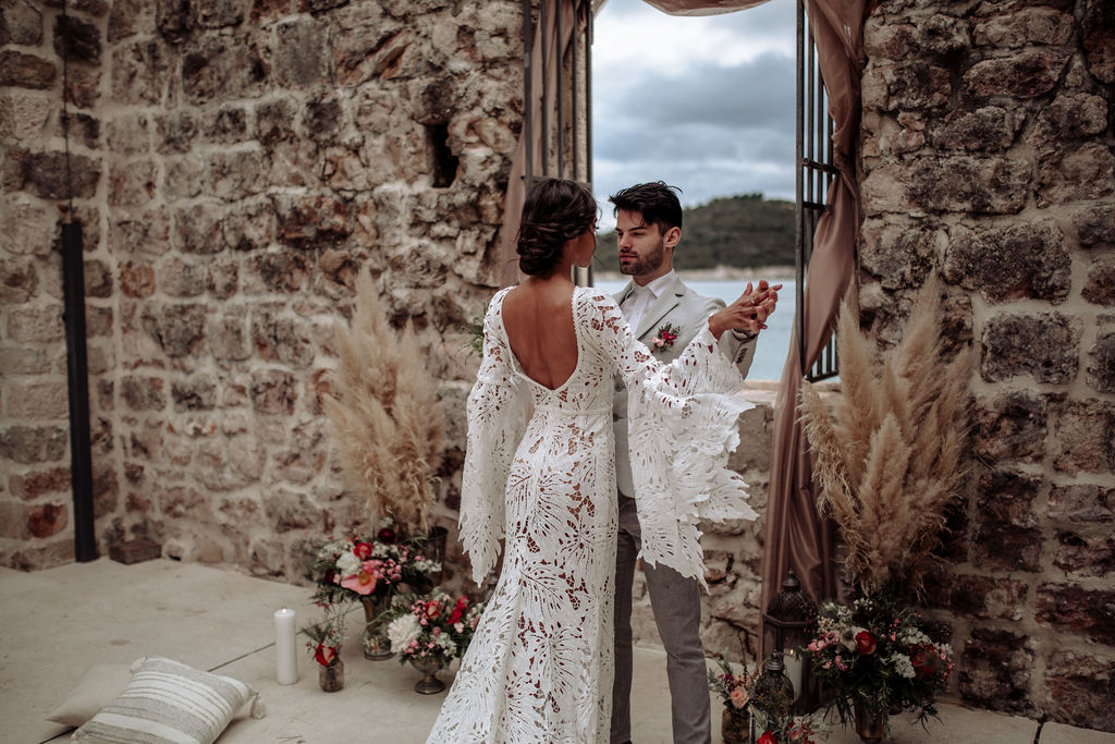 This is a photo of a beautiful couple. She has an open back lacy wedding dress and looks stunning in it. They are embracing and holding hands as if they are dancing. Her eyes are closed as she is enjoying the moment.