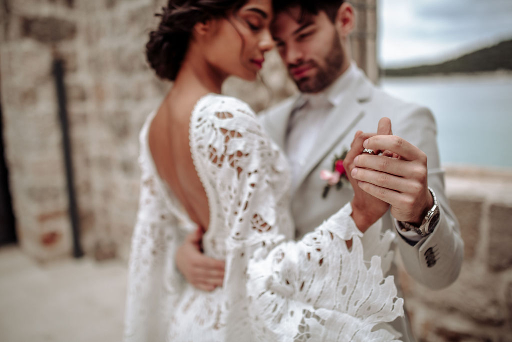 This is an intentionally blurry photo of a couple. She has an open back lacy wedding dress and looks stunning in it. They are embracing and holding hands as if they are dancing. Her eyes are closed as she is enjoying the moment.