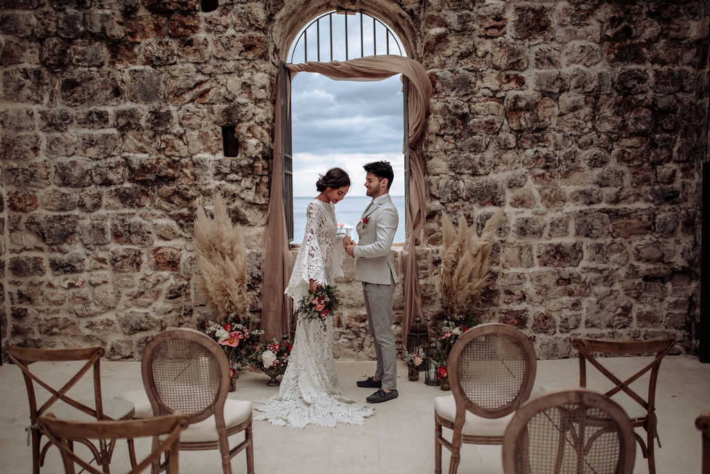 This image is from a styled photoshoot for an elopement in Dubrovnik. She's wearing a stunning long lace dress and he has a classic grey suit. This set up is for a ceremony. Behind them is a window with blush curtain fabric and pampas. The chairs are wooden Louis chairs.