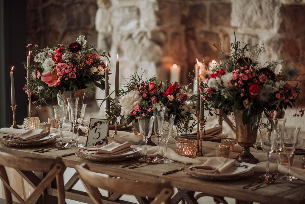 This image is a close up of a reception set up. The details are gold and rose gold. The runner on the wooden table and the main plate are both a very light shade of pink. The flower arrangements are a combination of wild flowers, greenery and roses.