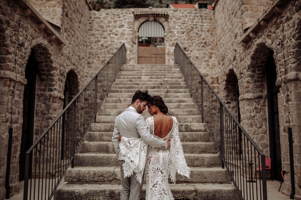 This image is from a styled photoshoot for an elopement in Dubrovnik. She's wearing a stunning long lace dress and he has a classic grey suit. They are on a big limestone staircase of the Lazareti complex in Dubrovnik.