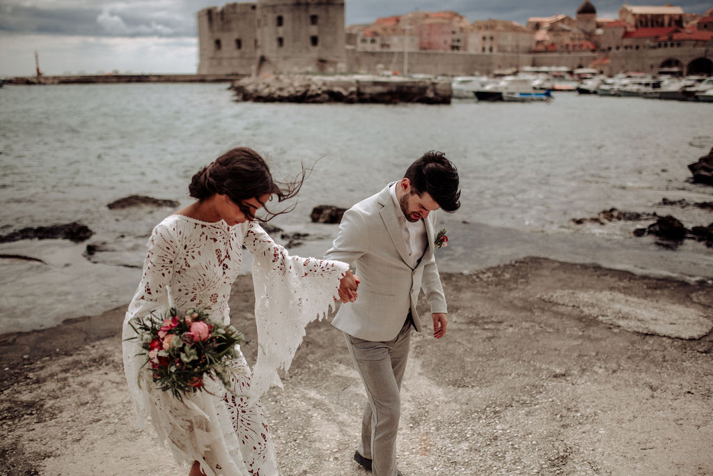 This image is from a styled photoshoot for an elopement in Dubrovnik. We can see a couple holding hands, she's wearing a stunning long lace dress and he has a classic grey suit. In the background is Dubrovnik old city and they are holding hands.