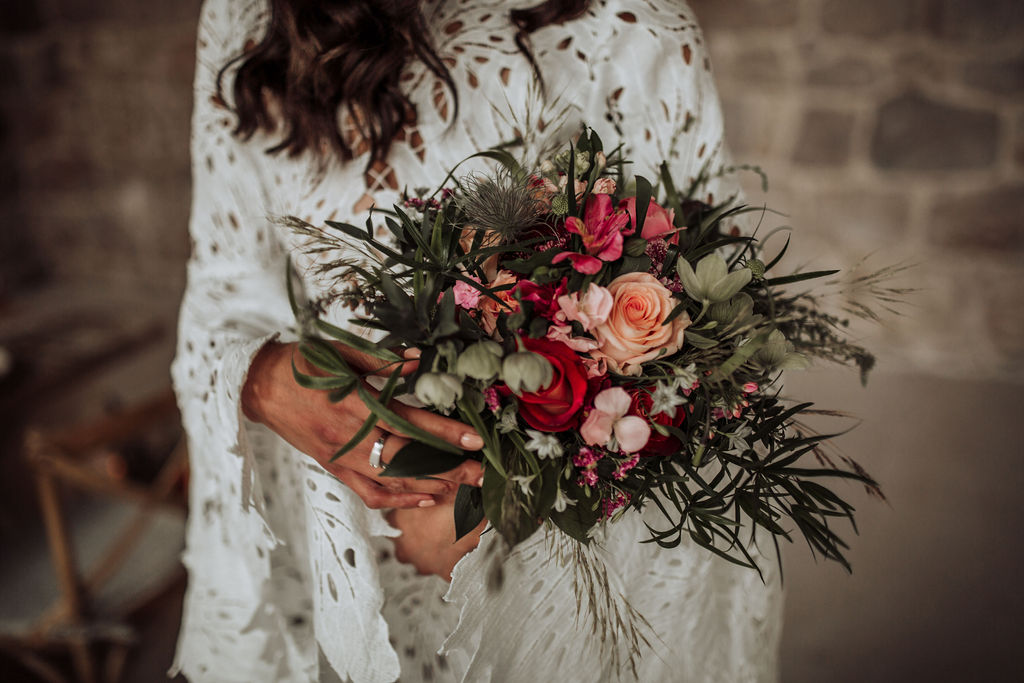 This image is a close up of a wedding bouquet for a styled photoshoot, made by Le Salon in Dubrovnik. It is a combination of greenery, wild flowers and red and pink roses. The bride is holding it while wearing a beautiful lace wedding dress.