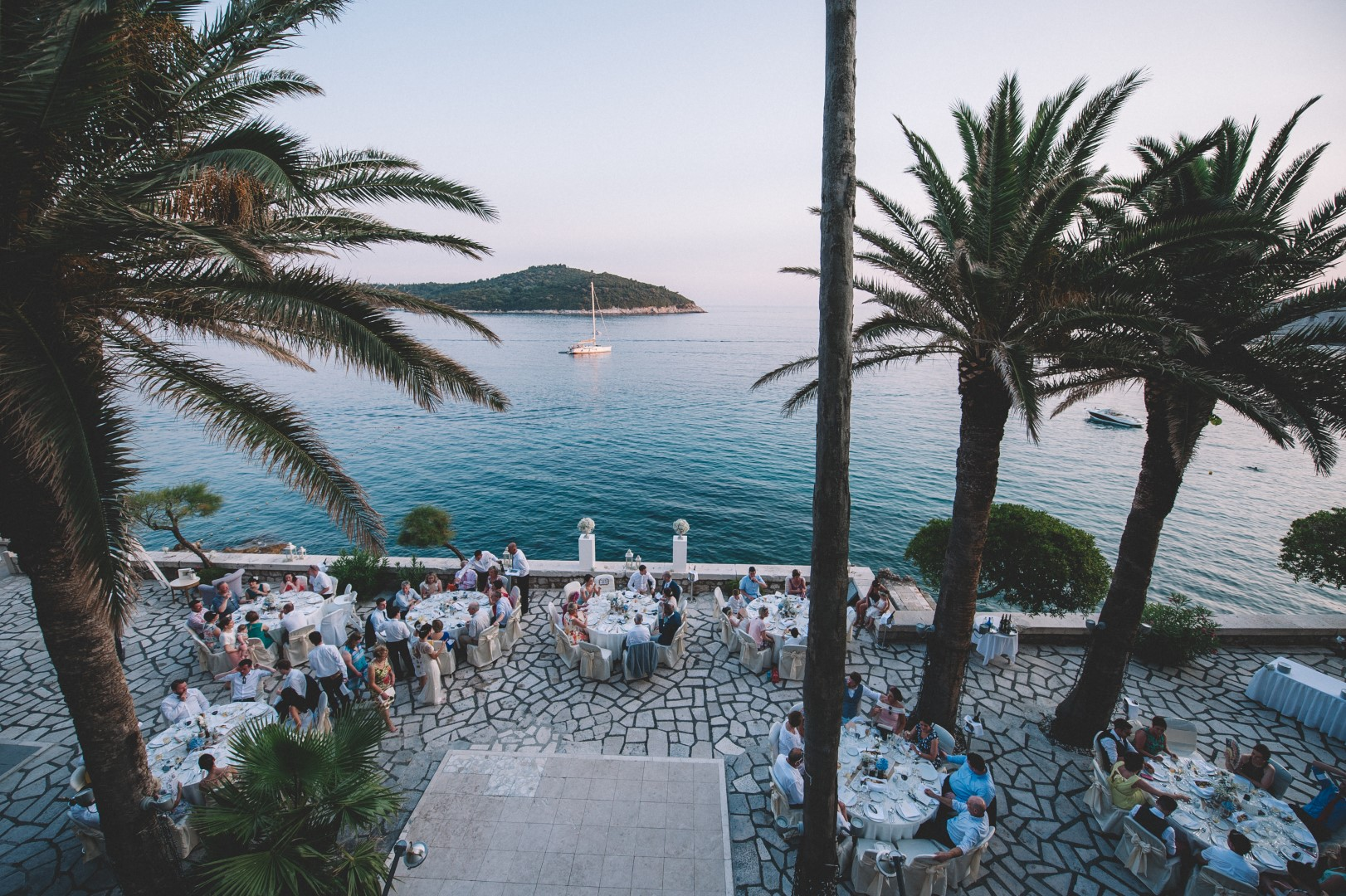 Dubrovnik terrace wedding, in the background is Lokrum island and we can see a wedding reception set up among the palm trees.