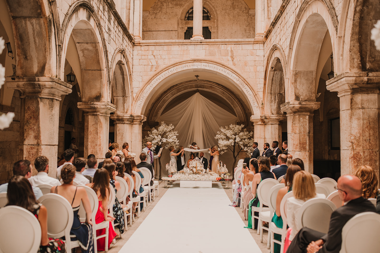 This image shows a popular Dubrovnik wedding venue: Sponza palace. This is a Persian wedding, the decoration is white and stunning, next to the couple are two fake white trees - very special.