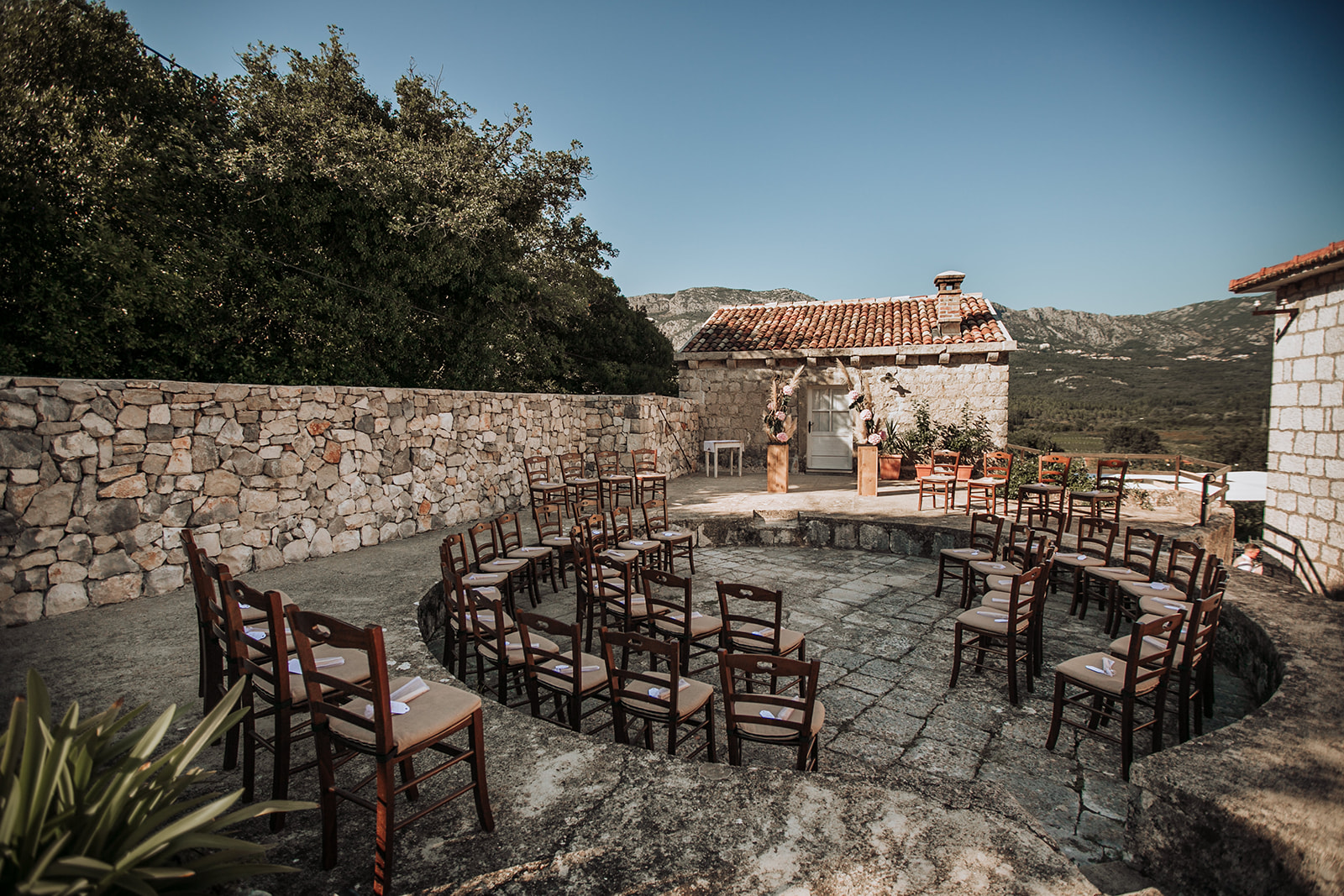 Image of a ceremony set up in Dubrovnik countryside. Stone walls and an old stone house. Chairs in a circle and a flower arch at the top for the couple. Mountains are in the background.