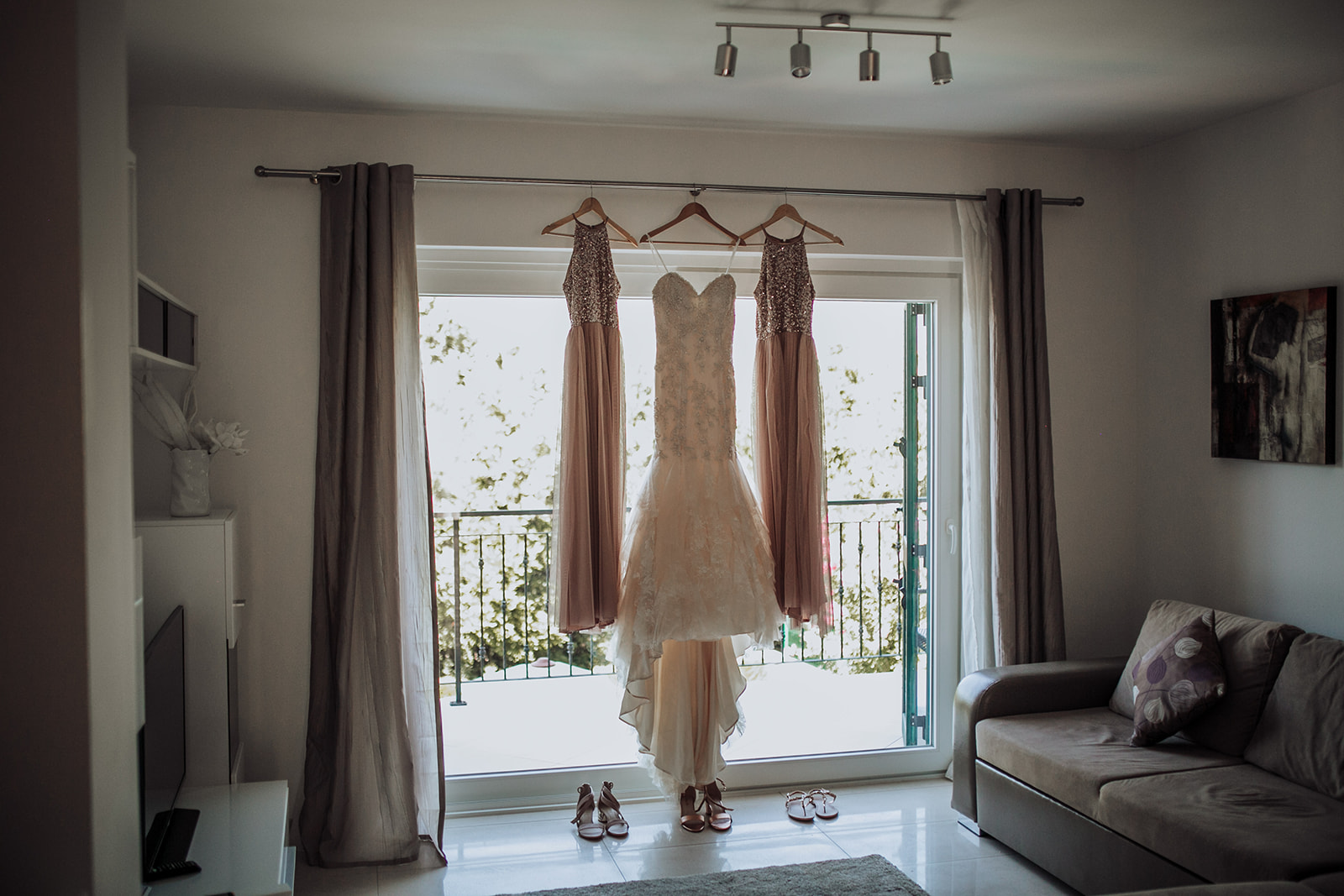 This photo shows the room where the bride and her bridesmaids are getting ready. On the big balcony window we can see her lovely wedding dress hanging surrounded by two pink dresses.