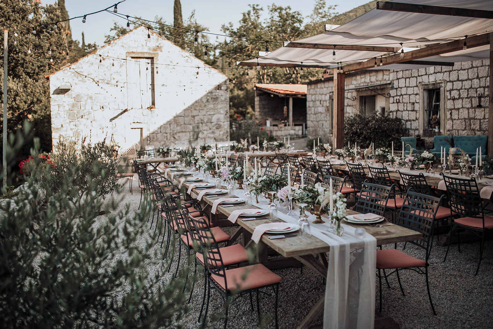A lovely photo from a countryside wedding in Konavle, next to Dubrovnik. The whole scene looks like Tuscany. There are fairy lights above them and you can see a stone house in the background.