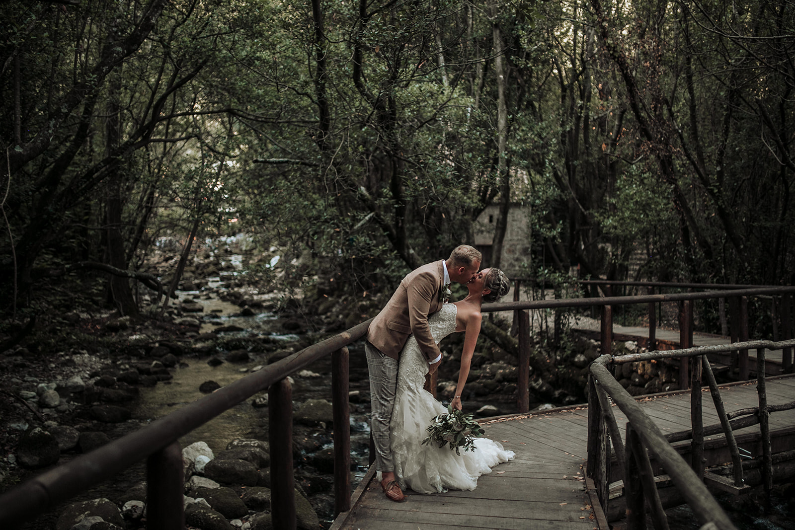 This image by Martina Škrobot Photography shows a happy couple on a wooden bridge next to a river. He is leaning the bride backwards and giving her a kiss.