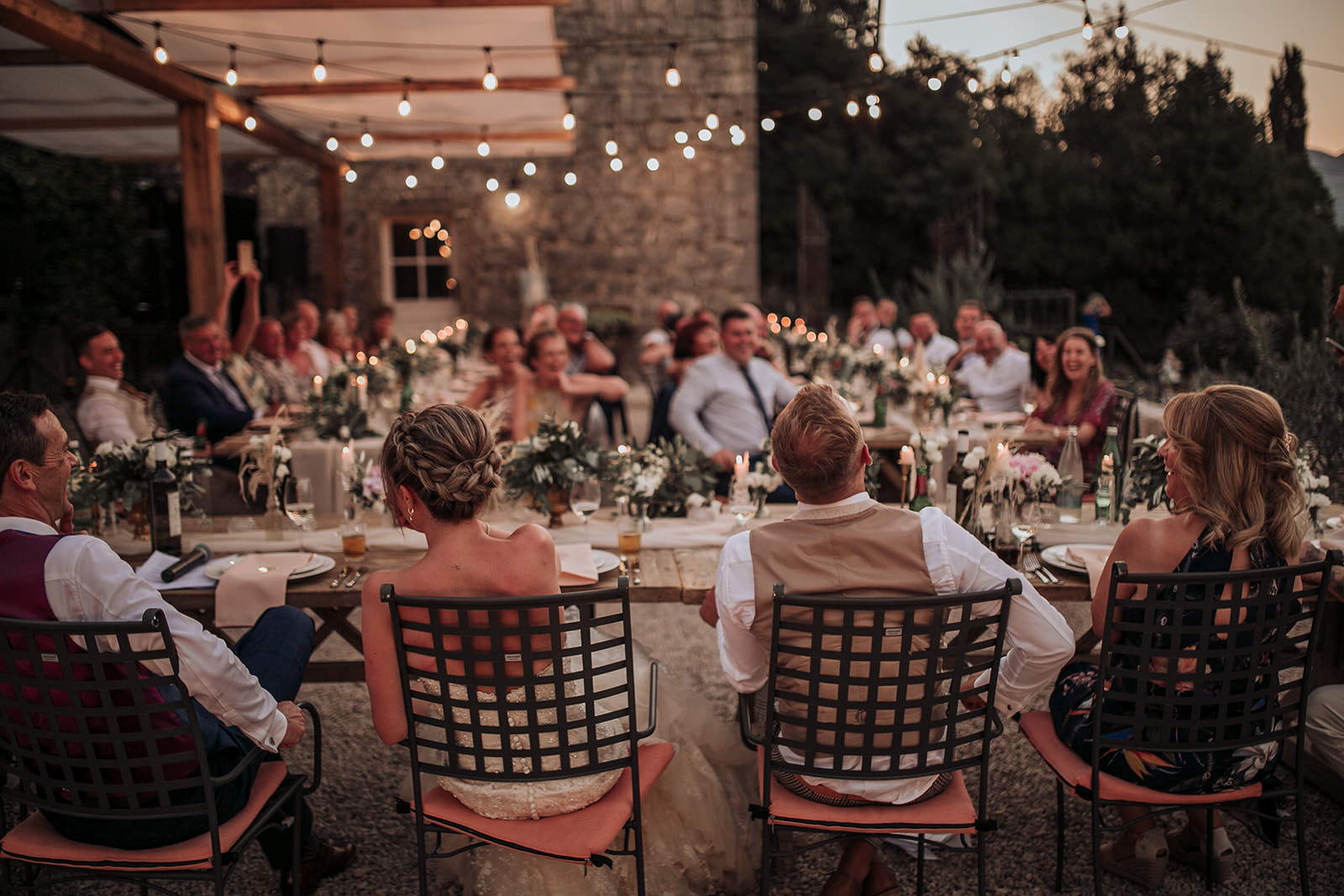 A lovely photo from a countryside wedding in Konavle, next to Dubrovnik. The whole scene looks like Tuscany. There are fairy lights above them and you can see a stone house in the background. Everyone is laughing together.