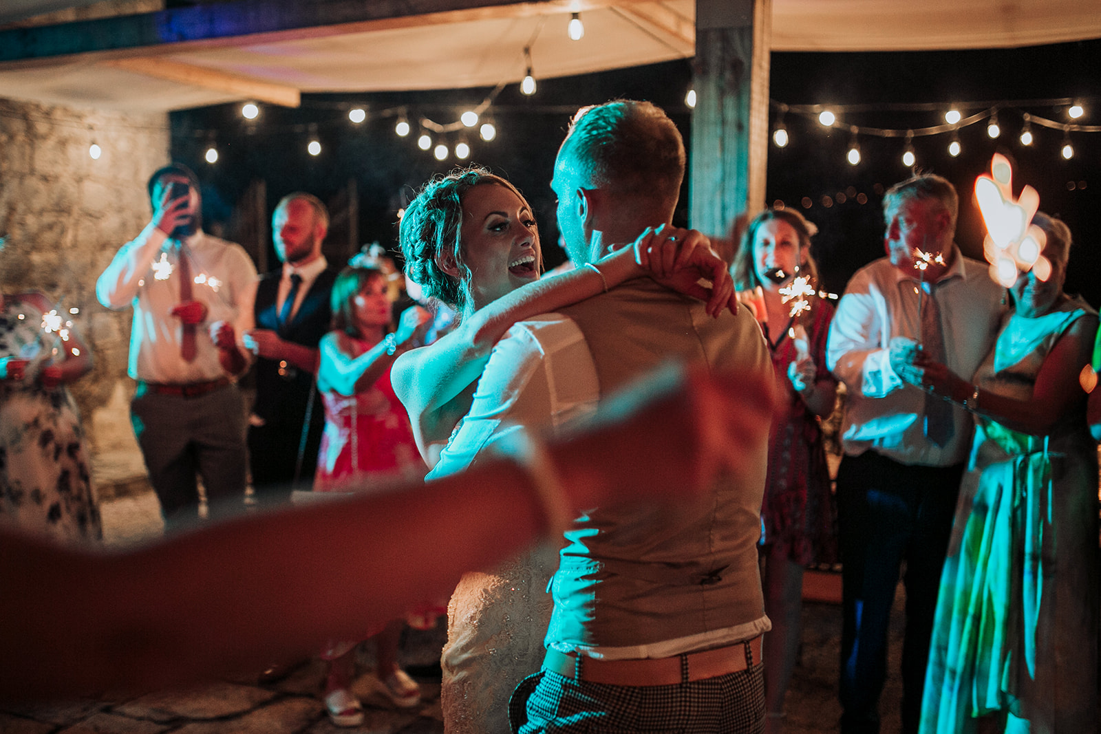 A cute photo of the happy wedding couple dancing. The bride is laughing. The guests are laughing as well and holding sparklers. One guest in the background is filming with his phone. The atmosphere looks great.