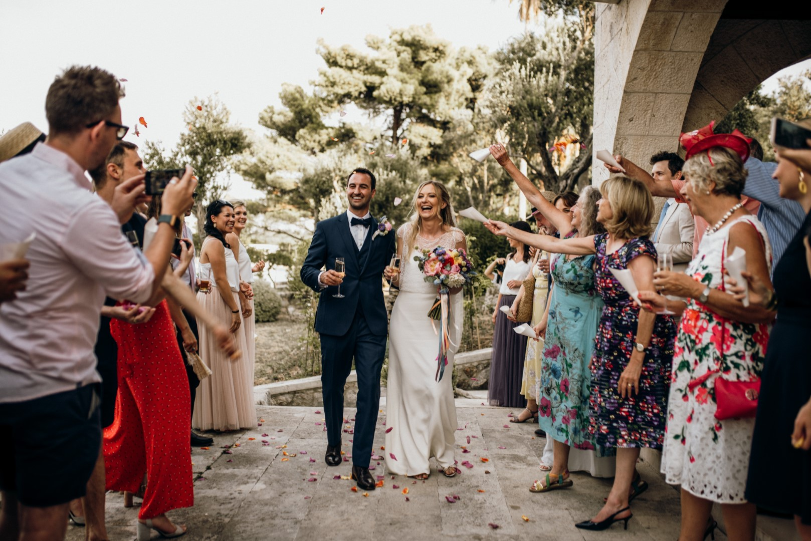 This photo shows a couple arriving to their wedding reception on Kolocep island. The wedding venue is Villa Ruza, a renowned restaurant in Dubrovnik area. Everyone around them is cheering and throwing confetti and flowers. The colors are beautiful and everyone is enjoying. The couple has two champagne glasses.